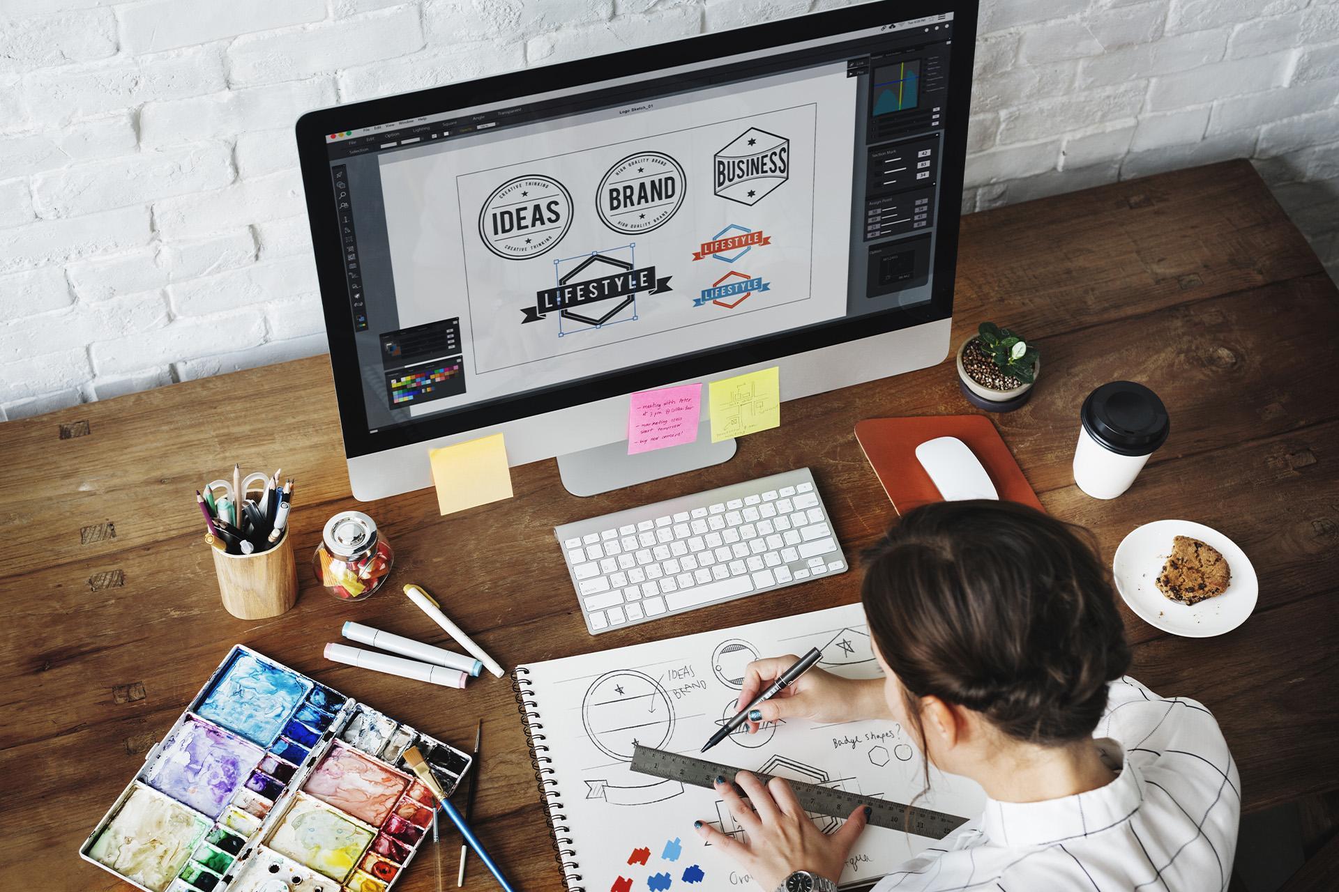 Diseñador gráfico bocetando y enfrente de su computadora con logos